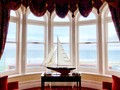 a-model-boat-in-a-bay-window-looking-out-to-sea-B8446N3